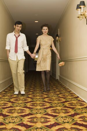 Young coupled dressed up walking down hotel hallway