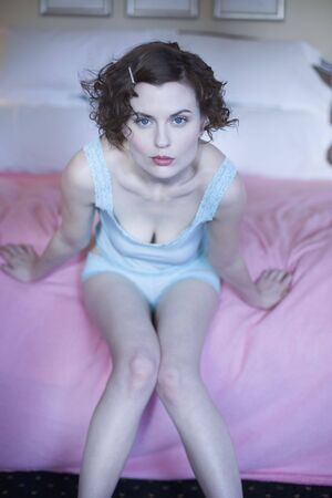 Woman leaning forward on bed in camisole and panties