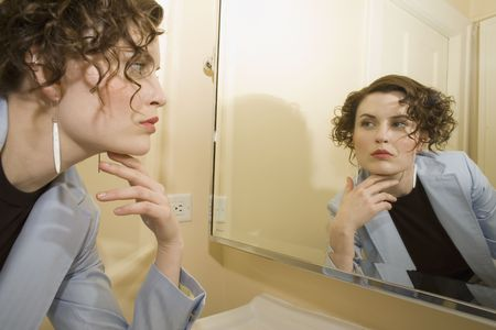 Woman looking in mirror with hand on chin