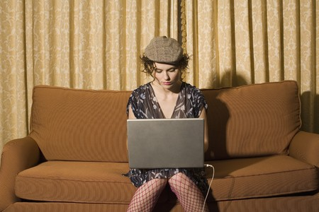 stood up: Woman sitting on sofa using laptop LANG_EVOIMAGES