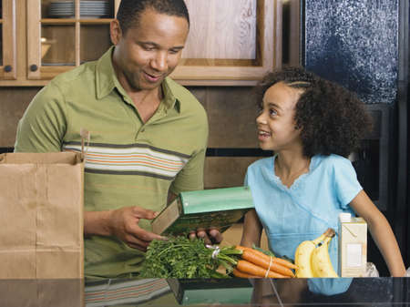 father daughter: African father and daughter with groceries in kitchen