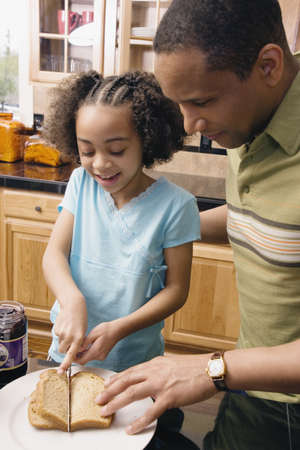 peanut butter and jelly sandwich: African father and daughter making peanut butter and jelly sandwich LANG_EVOIMAGES