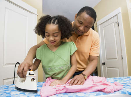 African father helping daughter use iron Stock Photo