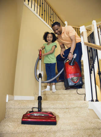poppa: African father and daughter vacuuming stairs LANG_EVOIMAGES