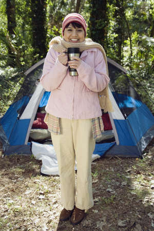babyboomer: Senior woman with thermos next to tent