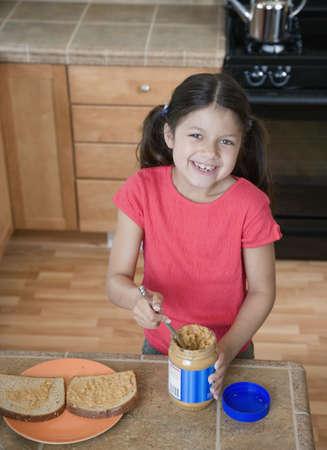 Hispanic girl making peanut butter and jelly sandwich Stock Photo