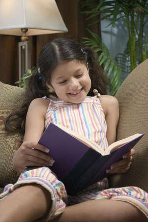 concluding: Hispanic girl reading on sofa LANG_EVOIMAGES