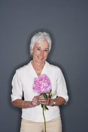 Senior woman holding flowers and smiling Stock Photo