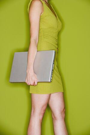motioning: Studio shot of woman holding laptop