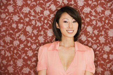 exclaiming: Asian woman smiling in front of floral wallpaper