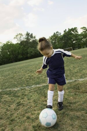 athletic gear: Young girl in athletic gear playing soccer