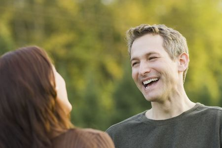 exactitude: Couple looking at each other and laughing outdoors