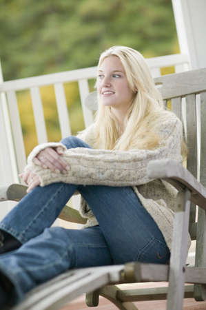 pjs: Young woman in sweater sitting on porch