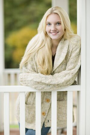 acknowledging: Young woman leaning on porch railing outdoors