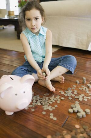 only one girl: Young girl counting money next to piggy bank