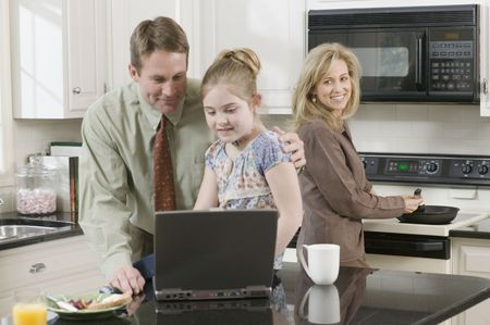 babyboomer: Family making breakfast and looking at laptop LANG_EVOIMAGES