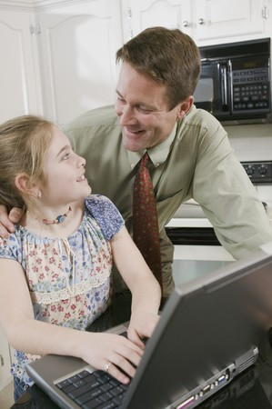 poppa: Father and daughter using laptop in kitchen