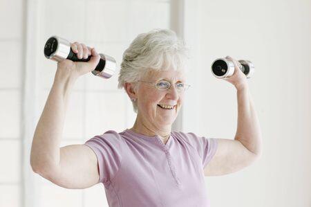 slumbering: Senior woman lifting free weights