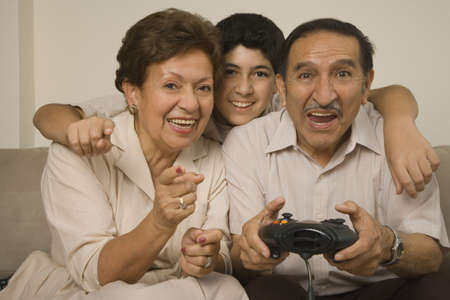 game viewing: Hispanic grandparents playing video games with grandson LANG_EVOIMAGES