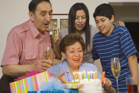 generation gap: Multi-generational Hispanic family with birthday cake