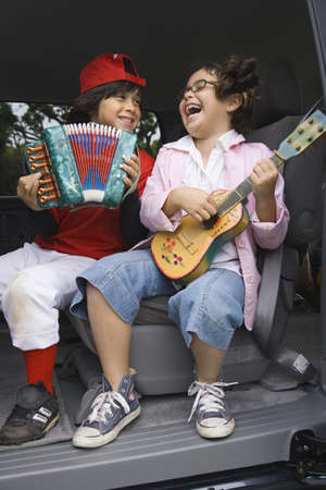 undisciplined: Brother and sister playing toy instruments in back of car LANG_EVOIMAGES