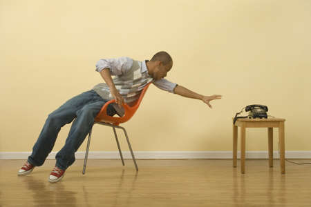 interrogating: African man stretching to reach telephone from chair