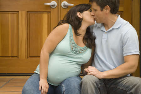 milepost: Pregnant couple kissing outdoors