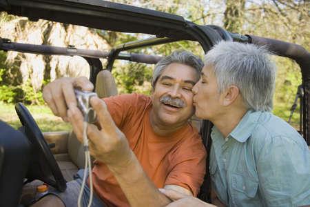 adoring: Senior Hispanic couple taking self-portrait with jeep