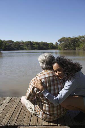 Couple hugging on wooden dock LANG_EVOIMAGES