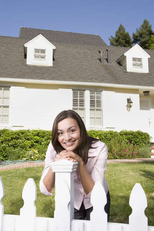 Woman smiling and leaning on fence in front of house