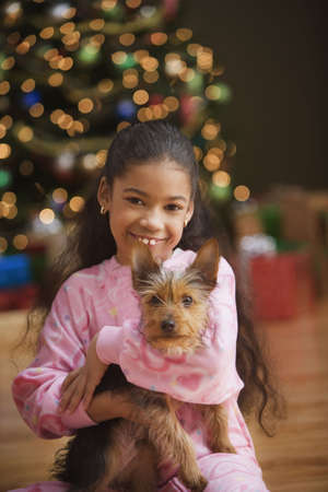 adoring: Girl holding Yorkshire Terrier puppy on Christmas