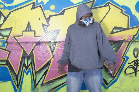 north western european descent: African man with spray paint next to graffitied wall