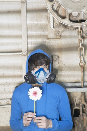 north western european descent: Young man wearing air filter mask and holding flower