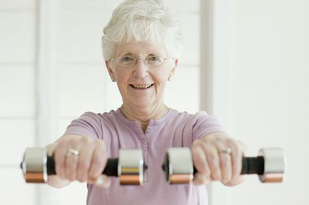 年配の女性が自由な重量を持ち上げる