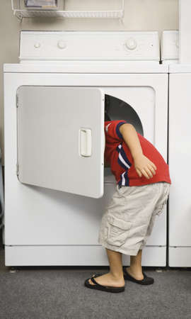 dryer: Young boy looking in dryer