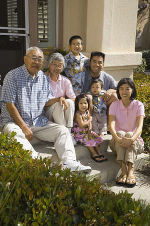 bambino: Multi-generational Asian family smiling on front steps of house LANG_EVOIMAGES