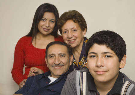 generation gap: Hispanic grandparents with adult daughter and grandson smiling LANG_EVOIMAGES