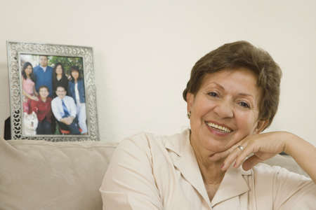 Senior Hispanic woman smiling next to photograph of family Stock Photo