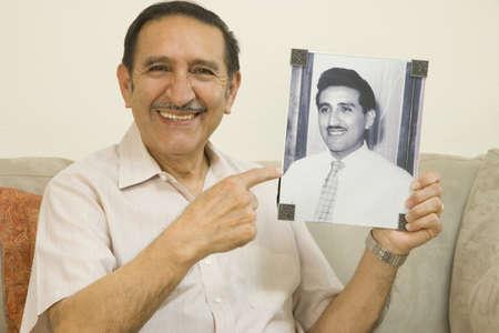 adoring: Senior Hispanic man smiling and holding photograph of younger self