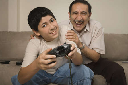 motioning: Hispanic grandfather laughing while grandson plays video game LANG_EVOIMAGES
