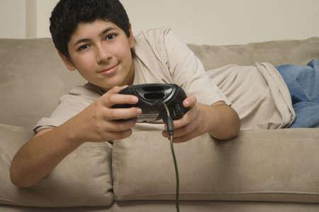 playing on divan: Hispanic boy laying on sofa playing video games LANG_EVOIMAGES