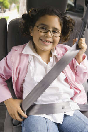misbehaving: Girl fastening seatbelt in backseat of car