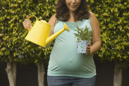 german ethnicity: Pregnant woman watering potted plant outdoors