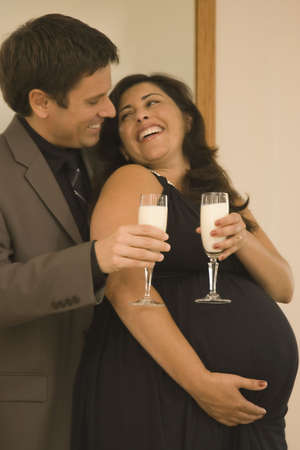two people fertility: Pregnant couple in fancy clothing toasting champagne glasses of milk LANG_EVOIMAGES
