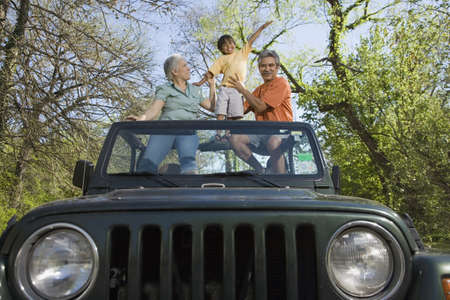babyboomer: Grandparents and grandson standing in jeep