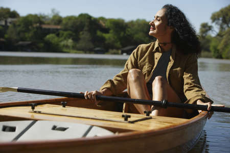 Woman sitting in canoe holding oar