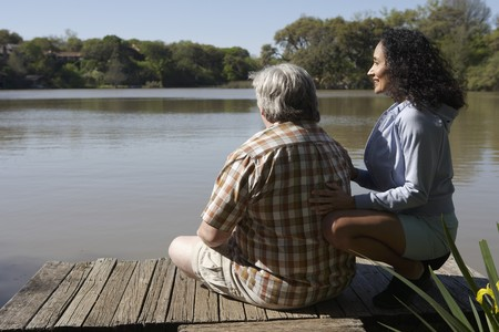 fathering: Couple sitting on wooden dock looking at water
