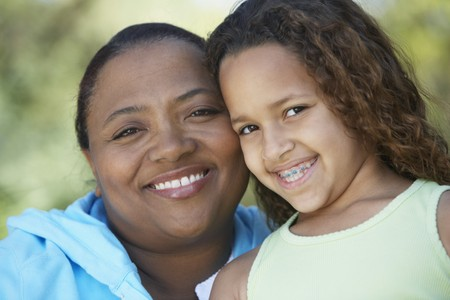 African mother and daughter with braces smiling Imagens