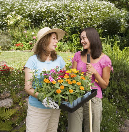 spectating: Two women with flat of plants in garden