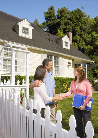Couple shaking hands with real estate agent Stock Photo